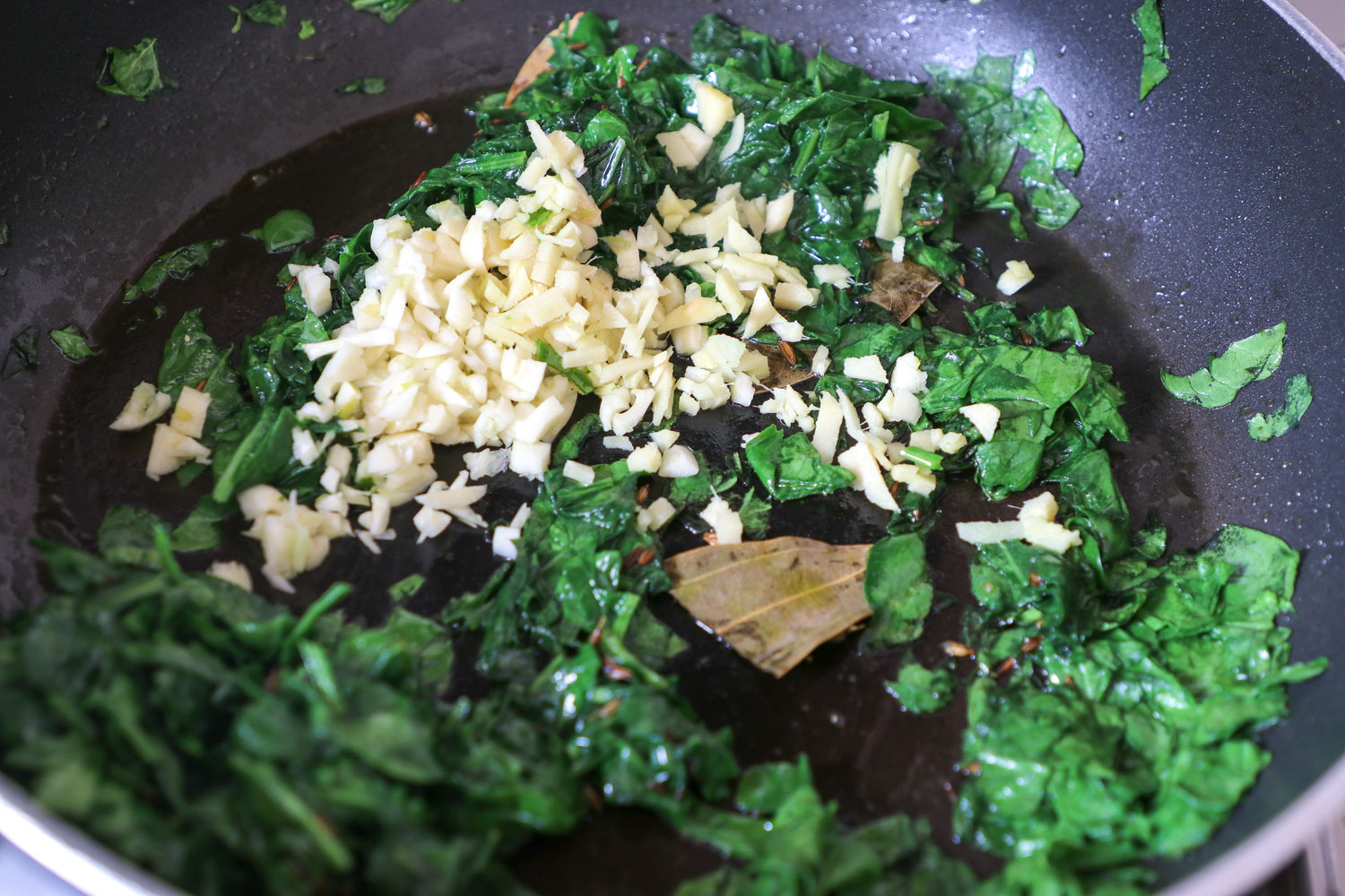 Adding chopped spinach and ginger garlic to the tempering