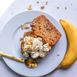 banana and walnut bread loaf slices topped with whipped cream , chopped walnuts and a drizzle of maple syrup