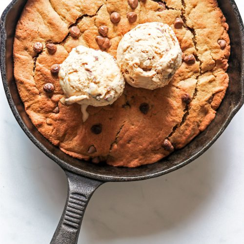 Skillet chocolate chip cookie topped with 2 scoops of ice cream