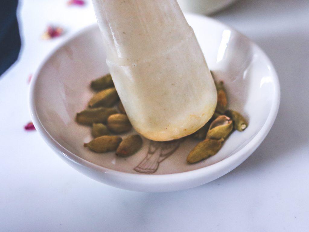 crushing cardamoms in mortar and pestle