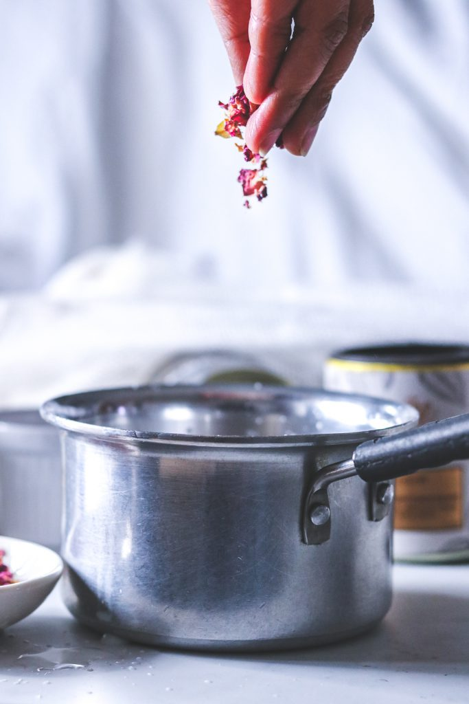 adding roses  and cardamoms to milk